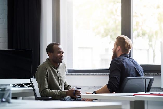 Twee jonge mannelijke collega's met elkaar praten