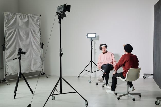 Twee jonge mannelijke vloggers in vrijetijdskleding, zittend op stoelen voor elkaar in de studio en interactie