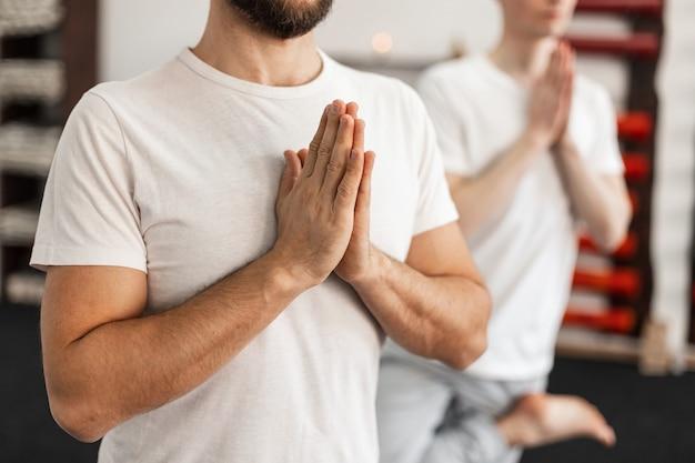 Twee jonge mannen beoefenen samen yoga in de sportschool. concept gezonde en sportieve levensstijl.