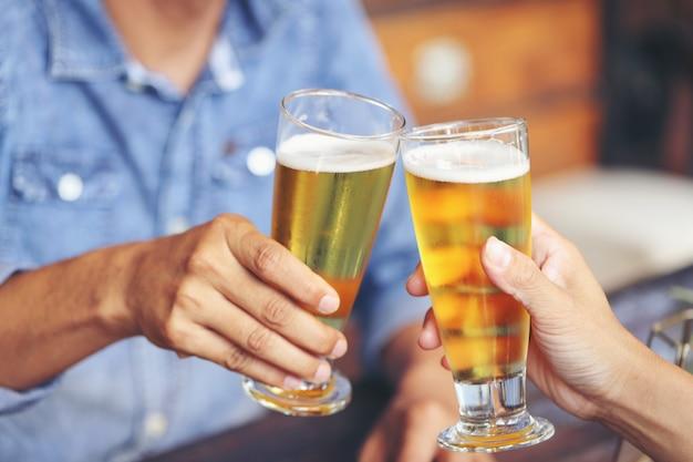 Twee jonge mannen botsen met twee glazen bier om hun succes te vieren.