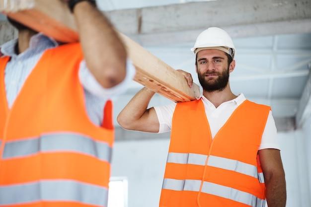 Twee jonge mannen bouwers die houten planken dragen op de bouwplaats close-up