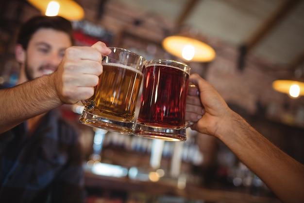 Twee jonge mannen die hun bierpullen roosteren