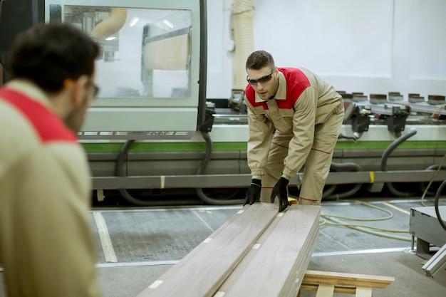 Twee jonge mannen die in de meubelfabriek werken