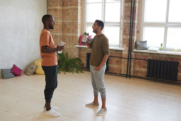 Twee jonge mannen die water drinken en met elkaar praten terwijl ze in de sporthal staan