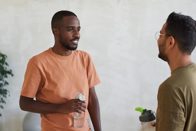 Twee jonge mannen drinkwater en praten in gezondheidsclub