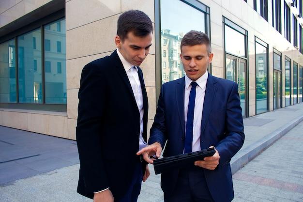 Twee jonge mannen in pakken tegen de achtergrond van een business center