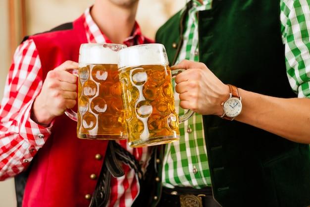 Twee jonge mannen in traditionele beierse klederdracht in restaurant of pub