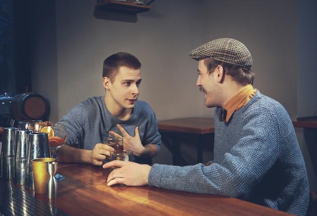 Twee jonge mannen in vrijetijdskleding praten zittend aan toog in pub