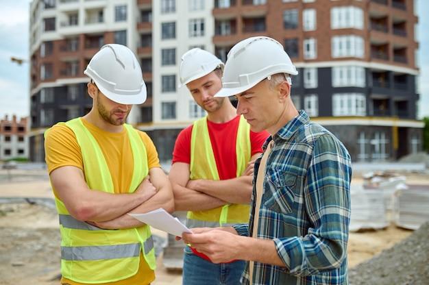 Twee jonge mannen met beschermende helmen en veiligheidsvesten staan bij een serieuze ingenieur van middelbare leeftijd met tekeningen