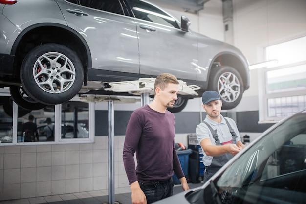 Twee jonge mannen staan in de garage op auto. werknemer wijst op automobiel. eigenaar kijkt ernaar.