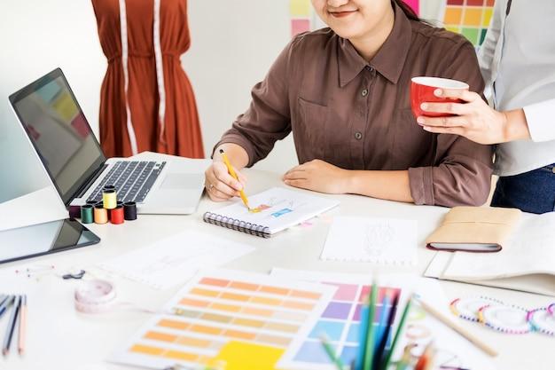 Twee jonge mannen werken als modeontwerpers en tekenen schetsen en krijgen stofadvies op maat.