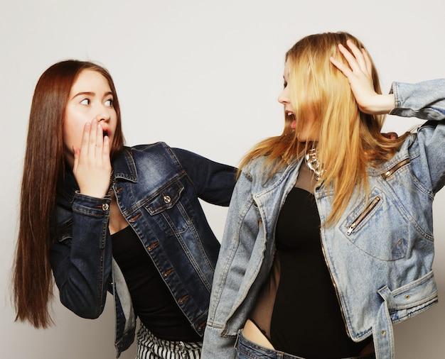 Twee jonge meisje hipster vrienden permanent samen, plezier hebben. over grijze achtergrond.