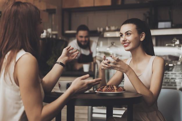 Twee jonge meisjes communiceren in een café aan de tafel