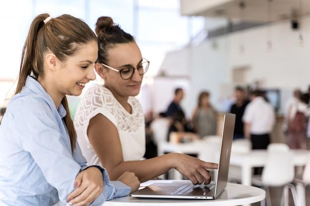 Twee jonge meisjes die samen met laptop in coworking werken