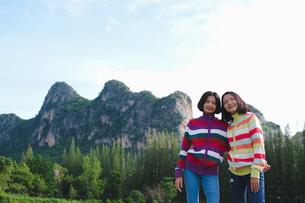 Twee jonge meisjes dragen truien die op een prachtig landschap staan.