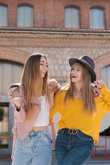 Twee jonge meisjes glimlachen en gelukkig op straat in het zonlicht