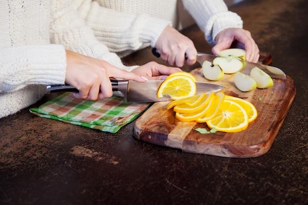 Twee jonge meisjes in de keuken die en fruit, gezonde levensstijl spreken eten