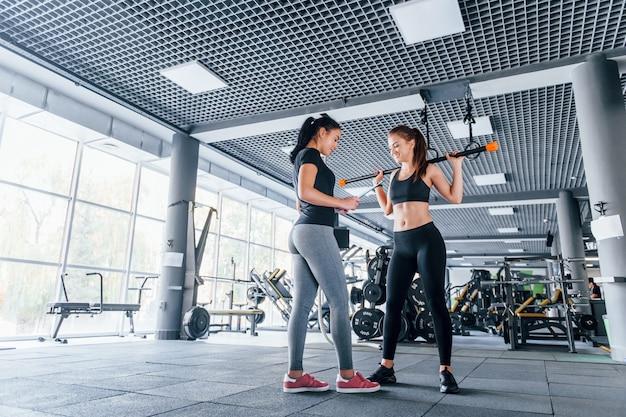 Twee jonge meisjes in sportieve kleding zijn overdag samen in de sportschool.