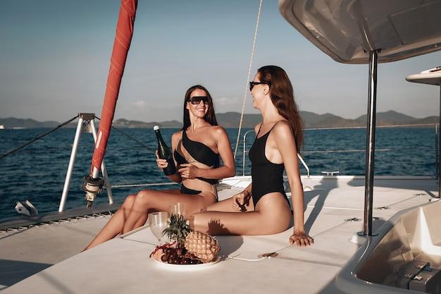 Twee jonge meisjes in zwarte bodysuit, zwembroek en zonnebril brengen graag hun zomervakantie door met champagne drinken op het jacht