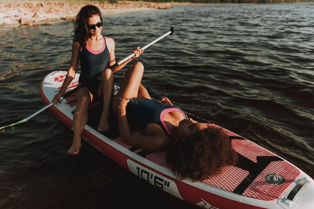 Twee jonge meisjes leggen samen op surf.