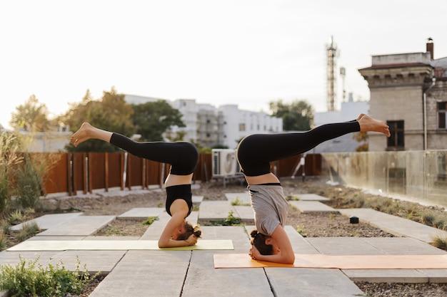 Twee jonge meisjes oefenen samen stretching en yoga training oefening