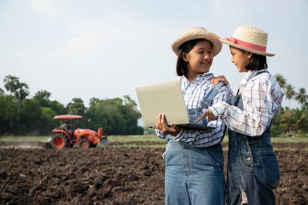 Twee jonge meisjes overlegden en planden het planten van maïs of sperziebonen met behulp van een computergestuurde laptop in het rijstveld tegen de achtergrond, terwijl vader de grond ploegde met een tractor op de boerderij