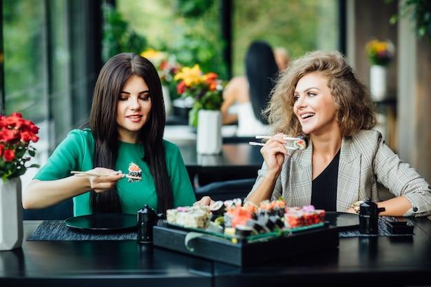 Twee jonge meisjes zitten in een restaurant op het zomerterras en brengen grappige tijd door met bord philadelphia.