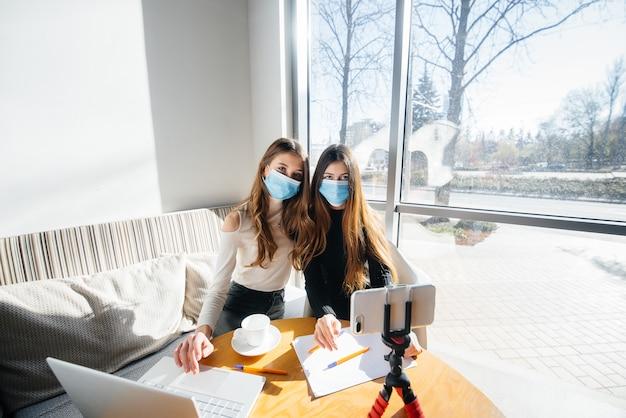 Twee jonge meisjes zitten met maskers in een café en leiden een videoblog. communicatie met de camera.
