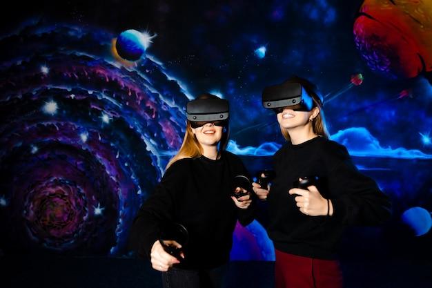 Twee jonge meisjes zussen vriend met virtuele bril hebben samen plezier en spelen videogames.