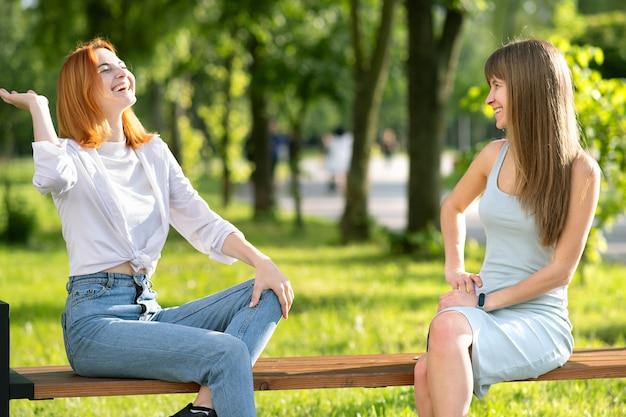 Twee jonge meisjesvrienden die op een bank in de zomerpark zitten die gelukkig pret babbelen.