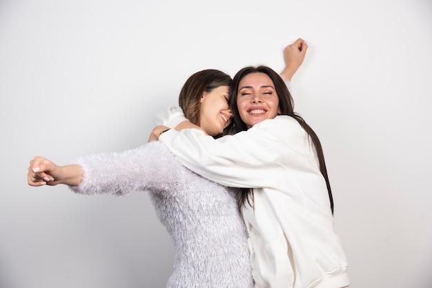 Twee jonge meisjesvrienden die pret hebben en op witte muur glimlachen.