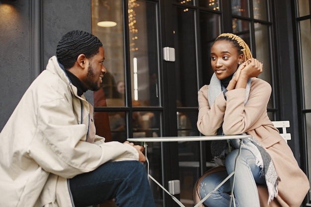Twee jonge mensen die buiten zitten. afrikaans paar dat van de tijd geniet die met elkaar doorbrengt.