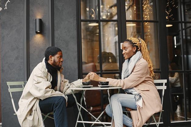 Twee jonge mensen die buiten zitten. afrikaans paar dat van de tijd geniet die met elkaar doorbrengt. Premium Foto