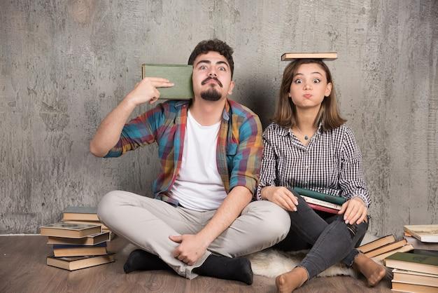 Twee jonge mensen die schattig met een heleboel boeken poseren