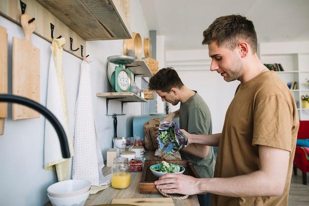 Twee jonge mensen die voedsel in keuken voorbereiden