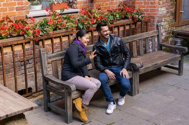 Twee jonge mensen, een jongen en een meisje die buiten op een bankje zitten, begroeten iemand