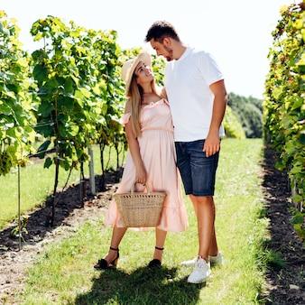 Twee jonge mensen in de druiventuin kijken elkaar met liefde aan
