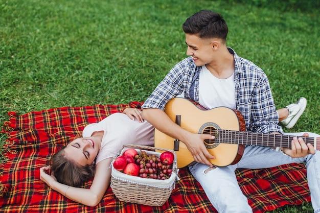 Twee jonge mensen in liefde die bij park rusten. jongen speelt op de gitaar.