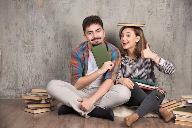 Twee jonge mensen poseren met een heleboel boeken en duimen opgevend