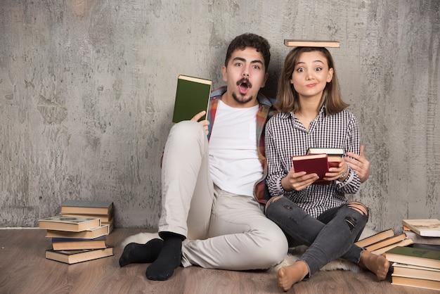 Twee jonge mensen poseren met een heleboel boeken