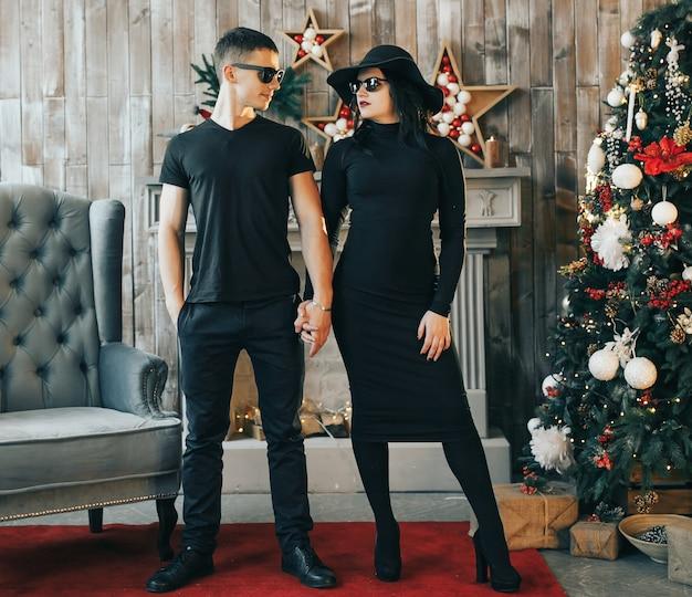 Twee jonge mensen staan voor een open haard in de buurt van de kerstboom