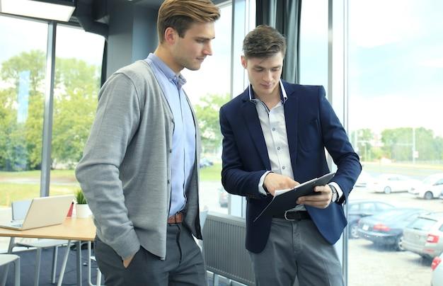 Twee jonge moderne mannen bespreken werk op kantoor.