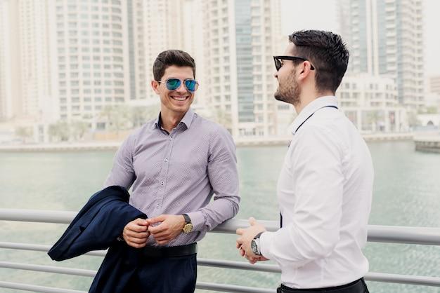 Twee jonge moderne zakenman in dubai marine leunde op hek. staan en discussiëren over zaken.