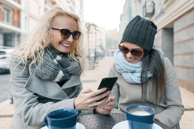 Twee jonge modieuze vrouwen die pret in openluchtkoffie hebben