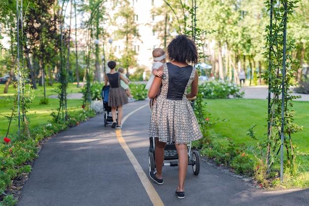 Twee jonge moeders die kinderwagens in de zomerpark duwen.