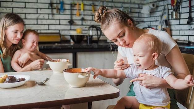 Twee jonge moeders geven samen hun gelukkige baby's melkpap in de keuken