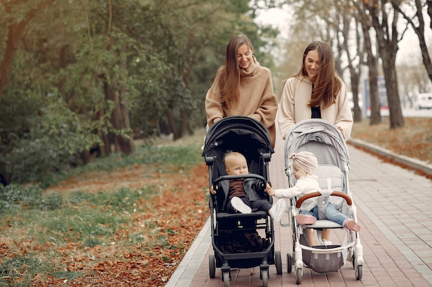 Twee jonge moeders lopen in een herfst park met rijtuigen