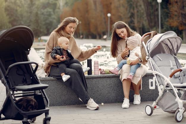Twee jonge moeders zitten in een herfst park met rijtuigen