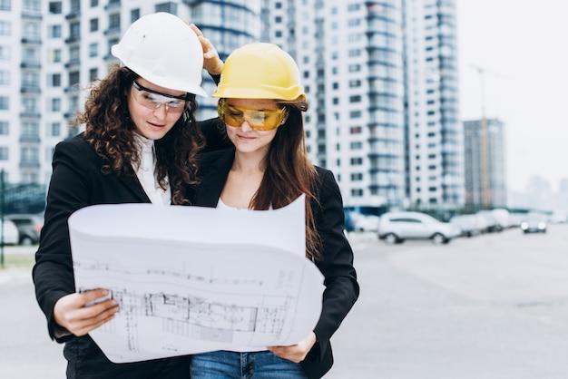 Twee jonge mooie bedrijfsvrouwen industriële ingenieurs in bouwhelmen op een glazen gebouw achtergrond. bouwplan, architect, ontwerper, succesvol