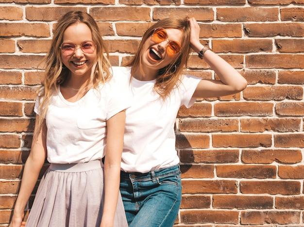 Twee jonge mooie blonde glimlachende hipster meisjes in trendy zomer wit t-shirt kleding. . positieve modellen die pret in zonnebril hebben